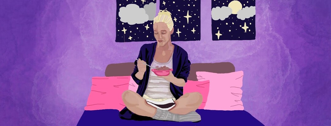 A woman at night sits on her bed eating cereal and reading a book in her lap