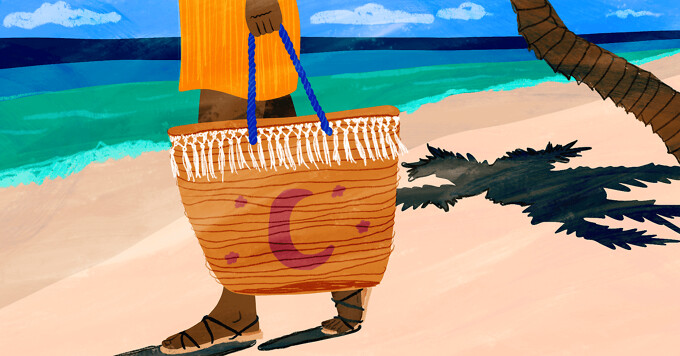 A woman walks down the beach holding a beach bag with a moon and stars on it
