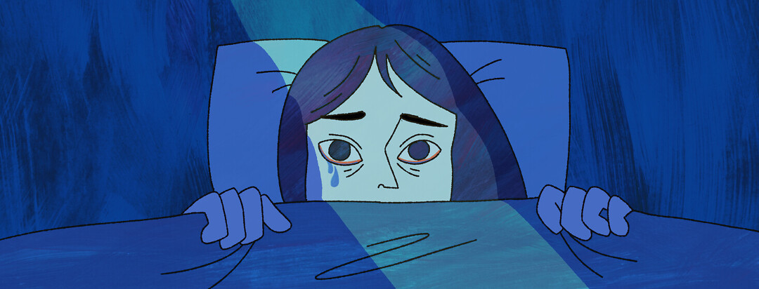 A woman laying awake in bed looking upset and sleep deprived